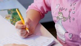 Den nätta lilla flickan gör hennes läxa på tabellen arkivfilmer