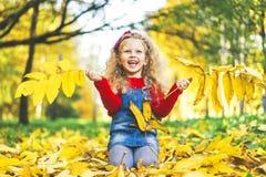 Den nätta lilla flickan har gyckel i parkera, hösttid royaltyfri fotografi
