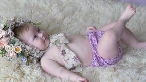 Den nätta lilla flickan i beslag med blommor ligger på filten och poserar på kameran på photoshoot arkivfilmer