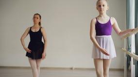 Den nätta lilla flickan i bodysuit och ballerinakjol har individuell balettövning som lär förehavanden och positioner med lager videofilmer