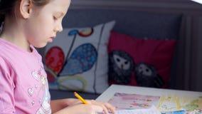 Den nätta lilla flickan lär att skriva på tabellen lager videofilmer