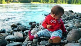 Den nätta lilla flickan sitter på en bank av bergfloden och spelar med stenar lager videofilmer