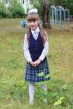 Den nätta lilla skolaflickan i likformig poserar i skola parkerar Royaltyfria Bilder
