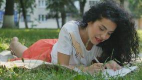 Den nätta lockiga brunetten kopplar av på plädet parkerar och skrivar in ett brev stock video