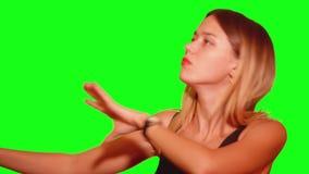 Den nätta longhairdflickan dansar framme av stående sida för kamera på lager videofilmer
