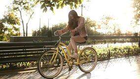 Den nätta longhaired flickan som rider en cykel på gatan, eller boulevarden i sommarstad parkerar Bärande rosa färger färgade til lager videofilmer