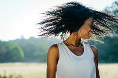 Den nätta lyckliga afrikanska flickan med naturligt smink skakar hennes långa lockiga hår och tycker om musik i hennes hörlurar Arkivfoto
