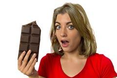 Den nätta lyckliga och upphetsade flickan som rymmer den stora chokladstången i sockerböjelsefrestelsen som ser skyldigt överhopp royaltyfria foton