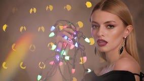 Den nätta modemodellen spelar med den elektriska girlanden i bokehbakgrund för gula ljus, ultrarapid lager videofilmer