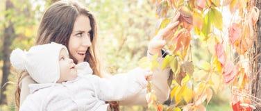 Den nätta modern med henne behandla som ett barn utomhus- på hösten parkerar Royaltyfri Fotografi