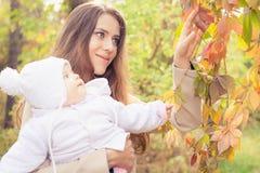 Den nätta modern med henne behandla som ett barn utomhus- på hösten parkerar Royaltyfri Bild