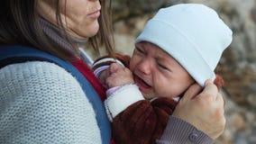 Den nätta modern med ryggsäcken som lugnar och kramar att gråta, behandla som ett barn pojken stock video