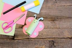 Den nätta pappers- fjärilen, sax, markören, limpinne, färgrikt papper täcker på en trätabell Idérika pappers- hantverk för barn Royaltyfri Fotografi