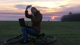 Den nätta rödhåriga flickan använder bärbara datorn och gör selfie nära kommunikationsradar lager videofilmer