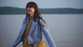 Den nätta romantiska kvinnan går nära sjön på aftonen lager videofilmer