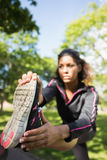Den nätta sportiga kvinnan som sträcker hennes ben parkerar in Arkivfoto