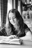 Den nätta studentflickan läser en bok i ett kafé Royaltyfria Bilder