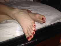 Den nätta tåfoten målade rött nailpolish arkivfoton