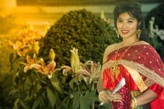 Den nätta thailändska damen i mellersta thailändskt klassiskt traditionellt frackanseende och hållgirland poserar på parkerar bak royaltyfri foto