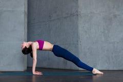 Den nätta tunna kvinnan i sportar behån och damasker som gör den uppåtriktade belägen mitt emot plankan för yoga, poserar, purvot arkivfoton