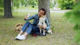 Den nätta ung flickabloggeren tar selfie med rashunden i stad parkerar utomhus den härliga keln och att smeka lager videofilmer