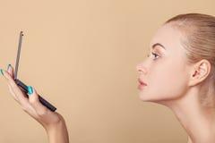 Den nätta unga blonda flickan kontrollerar hennes utseende Arkivfoton
