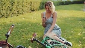Den nätta unga blonda kvinnan i en stilfull vit klänning och moderiktiga fnissanden sitter på gräsmattan i staden parkerar vid gr lager videofilmer