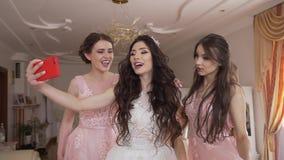 Den nätta unga bruden med nätt smink och långt lockigt hår tar roliga selfies med två älskvärda brudtärnor hemma stock video