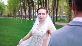 Den nätta unga bruden som går runt om brudgummen i soligt, parkerar stock video