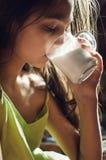 Den nätta unga brunetten som tycker om ett exponeringsglas av, mjölkar hemma och att le royaltyfri bild