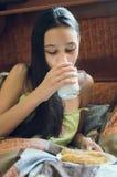 Den nätta unga brunetten som tycker om ett exponeringsglas av, mjölkar hemma och att le royaltyfri foto