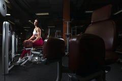 Den nätta unga brunettflickan kopplar av i benets utbildande apparatur i idrottshallen arkivbild