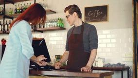 Den nätta unga damen köper takeaway coffe i coffee shop och betalar med smartphonen som gör contactless betalning modernt lager videofilmer