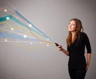 Den nätta unga damen som rymmer en telefon med färgrikt abstrakt begrepp, fodrar a Arkivbilder
