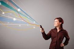 Den nätta unga damen som rymmer en telefon med färgrikt abstrakt begrepp, fodrar a Royaltyfria Bilder