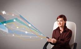 Den nätta unga damen som rymmer en telefon med färgrikt abstrakt begrepp, fodrar a Arkivfoto