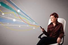 Den nätta unga damen som rymmer en telefon med färgrikt abstrakt begrepp, fodrar a Royaltyfri Bild