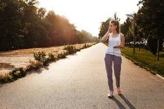 Den nätta unga flickan i sport beklär att gå på vägen och lyssnar musik på hennes smartphone royaltyfria foton