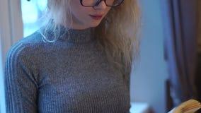 Den nätta unga flickan med exponeringsglas läser boken, medan stå nära fönstret Det lyckliga ung flickainnehav hänger lös på en v lager videofilmer