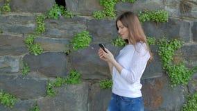 Den nätta unga flickan promenerar tappningväggen av den lösa stenen och användasmartphonen stock video