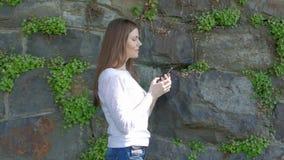 Den nätta unga flickan promenerar tappningväggen av den lösa stenen och användasmartphonen arkivfilmer