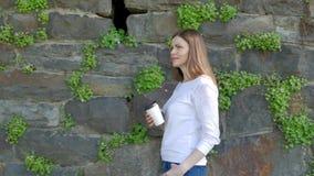 Den nätta unga flickan promenerar tappningväggen av den lösa stenen och drickakaffe stock video