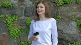 Den nätta unga flickan promenerar tappningväggen av den lösa stenen och drickakaffe arkivfilmer