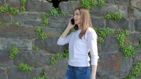 Den nätta unga flickan promenerar tappningväggen av den lösa stenen och samtal på smartphonen lager videofilmer
