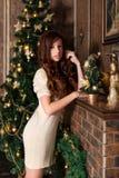 Den nätta unga flickan står nära en dekorerad spis och en julgran royaltyfri foto