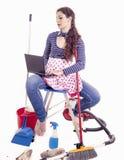 Den nätta unga hemmafrun konsulterar din bärbar dator i ett avbrott Arkivfoto