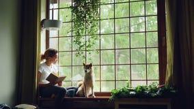 Den nätta unga kvinnan är läseboksammanträde på fönsterbräda och att se utanför samman med den gulliga rashunden härligt stock video