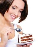 Den nätta unga kvinnan äter en söt kaka Arkivbild