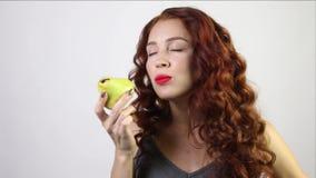 Den nätta unga kvinnan biter det nya päronet i den vita studion stock video