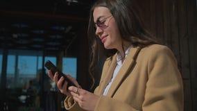 Den nätta unga kvinnan får sms på hennes mobiltelefon, att läsa och att le arkivfilmer